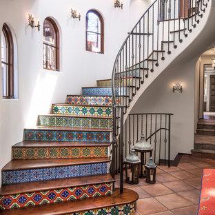 Diseño de escalera curva, mediterránea, con contrahuellas con baldosas y/o azulejos, escalones de madera y barandilla de metal