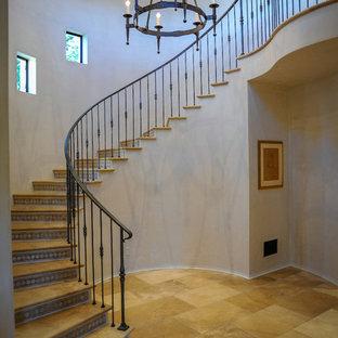 Стильный дизайн: большая изогнутая лестница в средиземноморском стиле с ступенями из травертина, металлическими перилами и подступенками из плитки - последний тренд