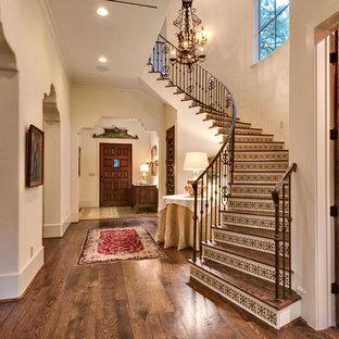 Foto på en stor medelhavsstil svängd trappa i trä, med sättsteg i kakel