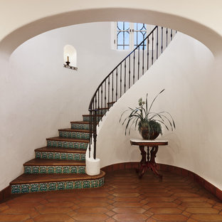 Imagen de escalera curva, mediterránea, grande, con contrahuellas con baldosas y/o azulejos, escalones de terracota y barandilla de metal