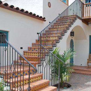サンタバーバラの中くらいのタイルの地中海スタイルのおしゃれなかね折れ階段 (タイルの蹴込み板) の写真