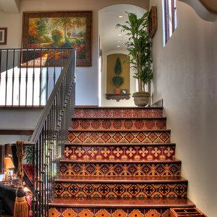 ロサンゼルスの木のサンタフェスタイルのおしゃれな階段 (タイルの蹴込み板、金属の手すり) の写真