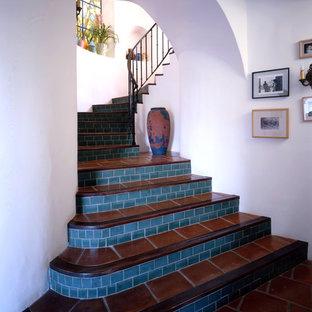 Ispirazione per una scala mediterranea con alzata piastrellata, pedata in terracotta e parapetto in metallo