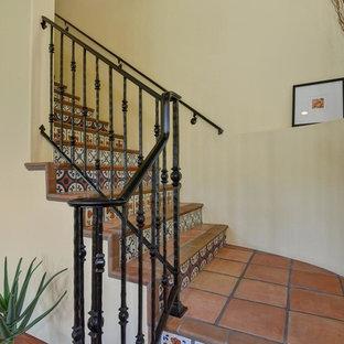 Modelo de escalera mediterránea con escalones de terracota, contrahuellas con baldosas y/o azulejos y barandilla de metal