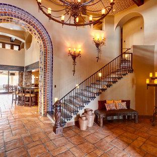 Foto de escalera mediterránea con escalones de madera, contrahuellas con baldosas y/o azulejos y barandilla de metal
