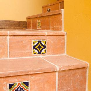 サンタバーバラの小さいタイルのサンタフェスタイルのおしゃれなかね折れ階段 (タイルの蹴込み板) の写真