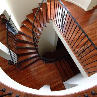 Foto di una grande scala curva classica con pedata in legno, alzata piastrellata e parapetto in metallo