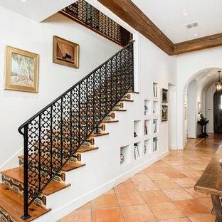 Ejemplo de escalera recta, mediterránea, con escalones de madera, contrahuellas con baldosas y/o azulejos y barandilla de metal