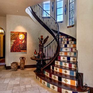 Imagen de escalera curva, mediterránea, con escalones de madera, contrahuellas con baldosas y/o azulejos y barandilla de metal