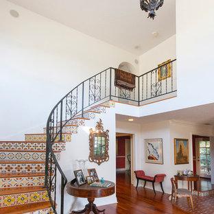 Imagen de escalera curva, mediterránea, con escalones de madera y contrahuellas con baldosas y/o azulejos