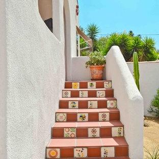Idee per una scala a rampa dritta stile americano con pedata in terracotta e alzata in terracotta