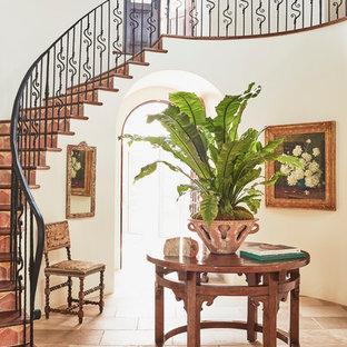 Ejemplo de escalera curva, mediterránea, extra grande, con barandilla de metal, escalones de piedra caliza y contrahuellas de terracota