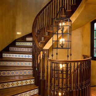 Diseño de escalera mediterránea con escalones de madera y contrahuellas con baldosas y/o azulejos