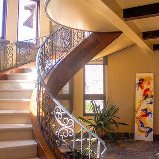 Новые идеи обустройства дома: большая изогнутая лестница в средиземноморском стиле с ступенями из известняка, подступенками из известняка и металлическими перилами