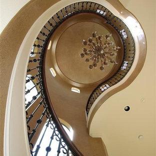 Ejemplo de escalera suspendida, mediterránea, extra grande, con escalones de madera, contrahuellas de travertino y barandilla de varios materiales