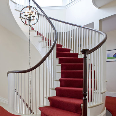 Example of a classic marble curved wood railing staircase design in Boston with painted risers