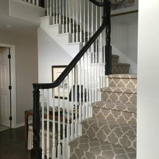 シアトルの中サイズのカーペット敷きのトラディショナルスタイルのおしゃれなかね折れ階段 (カーペット張りの蹴込み板、木材の手すり) の写真
