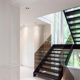 Foto de escalera en U, contemporánea, grande, sin contrahuella, con escalones de madera y barandilla de vidrio