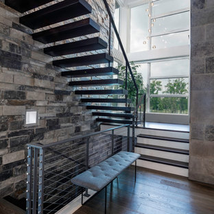 Ispirazione per una scala sospesa minimalista con pedata in legno, nessuna alzata e parapetto in metallo