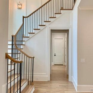 Ejemplo de escalera en U y boiserie, tradicional, grande, con escalones de madera, contrahuellas de madera pintada, barandilla de madera y boiserie