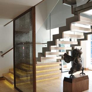 Modern inredning av en mellanstor flytande trappa i travertin, med öppna sättsteg och räcke i glas