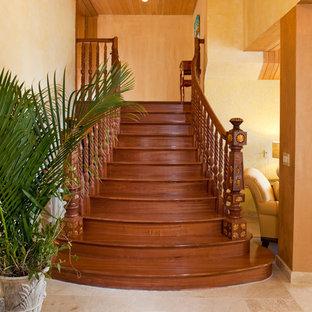 Diseño de escalera curva, mediterránea, de tamaño medio, con escalones de madera, contrahuellas de madera y barandilla de madera