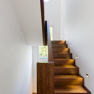На фото: класса люкс п-образные лестницы среднего размера в современном стиле с деревянными ступенями и деревянными подступенками
