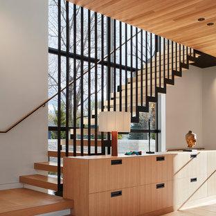Diseño de escalera en L, contemporánea, sin contrahuella, con escalones de madera y barandilla de metal
