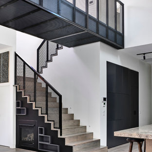 This is an example of a large contemporary wood u-shaped staircase in Melbourne with wood risers.