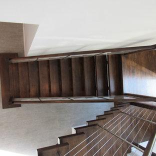 Immagine di un'ampia scala sospesa minimal con pedata in legno, nessuna alzata e parapetto in cavi