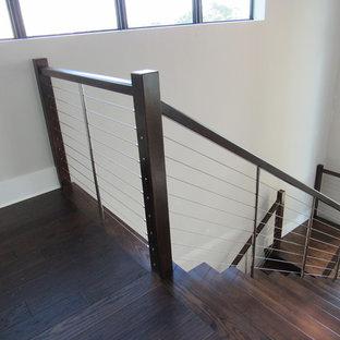 Esempio di un'ampia scala sospesa minimal con pedata in legno, nessuna alzata e parapetto in cavi