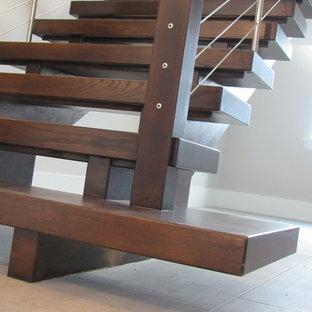 Foto di un'ampia scala sospesa contemporanea con pedata in legno, nessuna alzata e parapetto in cavi