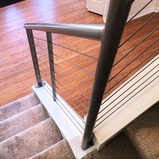 デトロイトの中くらいのカーペット敷きのコンテンポラリースタイルのおしゃれなかね折れ階段 (カーペット張りの蹴込み板、ワイヤーの手すり) の写真