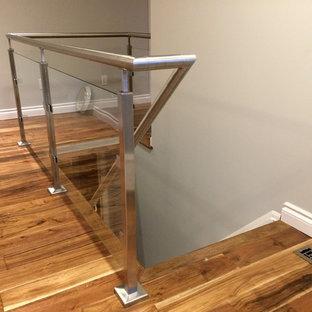 Ejemplo de escalera contemporánea con escalones de madera, contrahuellas de madera y barandilla de vidrio