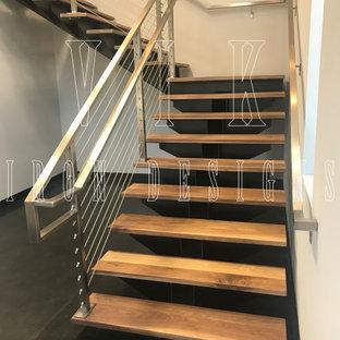 Imagen de escalera suspendida, contemporánea, de tamaño medio, con escalones de madera, contrahuellas de metal y barandilla de cable