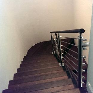 マイアミの中サイズの木のトランジショナルスタイルのおしゃれな折り返し階段 (木の蹴込み板、ワイヤーの手すり) の写真
