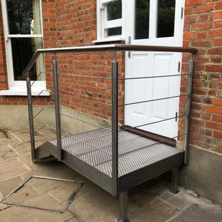Foto de escalera recta y ladrillo, contemporánea, pequeña, sin contrahuella, con escalones de metal, barandilla de metal y ladrillo