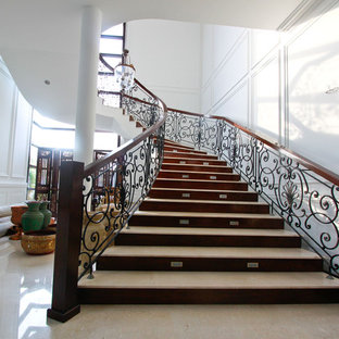 Ejemplo de escalera curva, mediterránea, con escalones de travertino, contrahuellas de madera y barandilla de metal