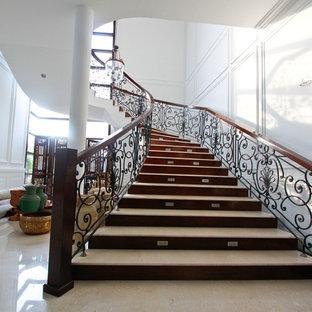 Idéer för att renovera en medelhavsstil svängd trappa i travertin, med sättsteg i trä och räcke i metall