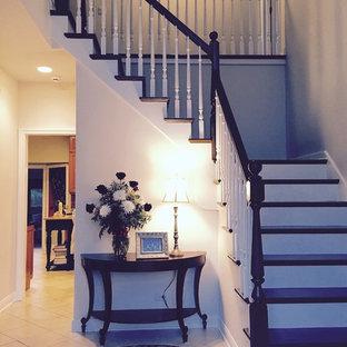 Diseño de escalera en L, tradicional renovada, de tamaño medio, con escalones de madera, contrahuellas de madera pintada y barandilla de madera