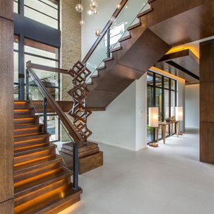 Imagen de escalera en U, actual, con escalones de madera, contrahuellas de madera y barandilla de varios materiales