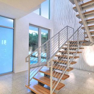 Foto de escalera suspendida, minimalista, grande, sin contrahuella, con escalones de madera y barandilla de metal