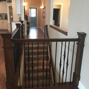Aménagement d'un escalier craftsman en L de taille moyenne avec des marches en moquette, des contremarches en moquette et un garde-corps en métal.