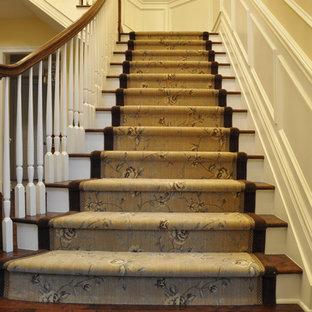 Diseño de escalera en L, tradicional, de tamaño medio, con escalones de madera y contrahuellas de madera pintada
