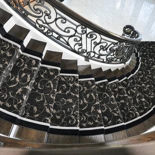 Réalisation d'un grand escalier courbe tradition avec des marches en bois et des contremarches en bois.
