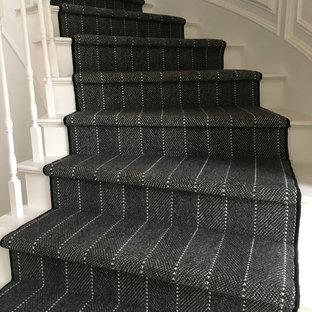 Ejemplo de escalera curva, tradicional renovada, de tamaño medio, con escalones de madera pintada, contrahuellas de madera pintada y barandilla de madera