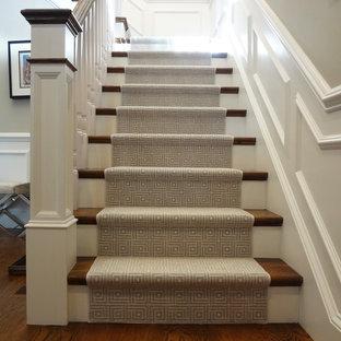 Idée de décoration pour un grand escalier tradition en L avec des marches en moquette et des contremarches en moquette.