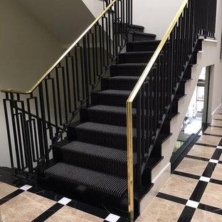 ロサンゼルスの広いフローリングのコンテンポラリースタイルのおしゃれな折り返し階段 (フローリングの蹴込み板) の写真