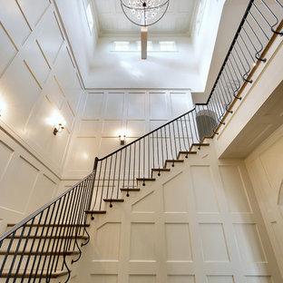 Diseño de escalera en L, tradicional, grande, con escalones de madera, contrahuellas de madera pintada y barandilla de metal