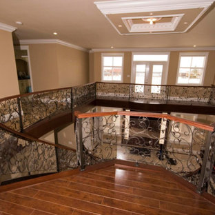 Staircase - huge traditional wooden curved open and mixed material railing staircase idea in Vancouver